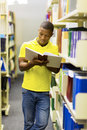 College boy reading book african a in library Royalty Free Stock Images