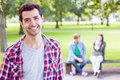 College boy smiling with blurred students sitting in park portrait of the Royalty Free Stock Photo