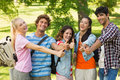 College friends gesturing thumbs up in campus group portrait of happy the Stock Image