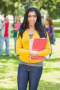 College girl holding books with blurred students in park portrait of standing the Royalty Free Stock Image