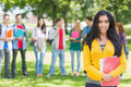 College girl holding books with blurred students in park portrait of standing the Stock Image