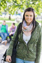 College girl smiling with blurred students in park portrait of sitting the Royalty Free Stock Photo
