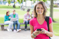 College girl text messaging with blurred students in park Royalty Free Stock Photo