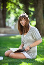 College student holding book portrait of sitting on campus lawn Stock Photography