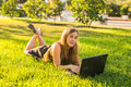 College student lying on the grass working on laptop at campus Royalty Free Stock Photo