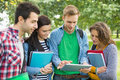 College students with bags and books using tablet pc in park group of young the Stock Photos