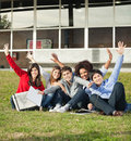 College students with hands raised sitting at portrait of carefree on grass campus Royalty Free Stock Photography