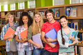 College students holding books in library group of the Stock Photography
