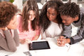 College students using a digital tablet multiethnic group of studying together Stock Images