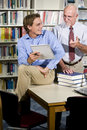 College teacher and student talking in library Stock Photo