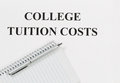 College tuition costs concept overhead view of white paper with wording of cost along with silver pen and notebook Stock Images