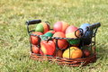 Collored easter eggs in a wicker work metal basket lying on the green grass Stock Photo