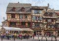 Colmar lifestyle france april rd people relaxing on street terraces in a town square near traditional half timbered houses in Stock Photography