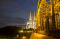 Cologne cathedral at night and part of the hohenzollern railway bridge in germany illuminated Royalty Free Stock Photography
