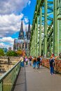 COLOGNE, GERMANY, AUGUST 11, 2018: People are passing on Hohenzollern bridge over Rhein during sunset, Germany Royalty Free Stock Photo