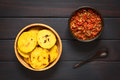 Colombian arepa with hogao sauce arepas in wooden bowl tomato and onion cooked and a spoon arepas are made of yellow or white corn Stock Photography