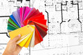 Color cart in hand man holding a set of paint swatches all the colors of the spectrum splayed out his background a construction Stock Image
