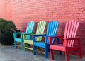 Color color color colorful chairs along a colorful wall Royalty Free Stock Photography