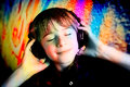 Color music little boy with headphone over colored background Stock Photography