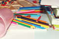 Color pencils and books are scattered on the children`s table. Royalty Free Stock Photo