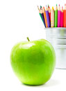 Color pencils in tin can or pencil holders and green apple bac great back to school supplies closeup Stock Image