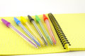 Color pens on the yellow writing book shallow dof Royalty Free Stock Photos