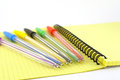 Color pens on the yellow writing book shallow dof Royalty Free Stock Images
