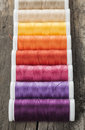 Color spools of sewing therads single row made threads on wooden background Stock Photos