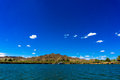 Colorado river and mountains and dredging barge under blue sky Royalty Free Stock Photo