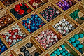 Colored beads in a wooden box divided with different shapes presented Stock Images