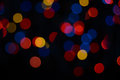 Colored bokeh defocused lights on the black background Stock Images