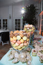 Colored cakes in glass containers at banquet table with large filled with sweet pastel macaroons or Stock Photography