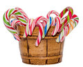 Colored candy sticks and Christmas lollipops in a brown vase, isolated, white background. Royalty Free Stock Photo