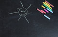 Colored chalks, black blackboard with drawings of the sun Royalty Free Stock Photo