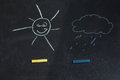 Colored chalks, black blackboard with drawings of sun and a cloud Royalty Free Stock Photo