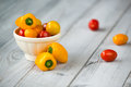 Colored cherry tomatoes and mini paprika in a bowl on a wooden t Royalty Free Stock Photo