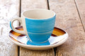 Colored coffee cup with saucer empty on wooden rustic table Royalty Free Stock Photos