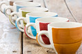 Colored coffee cups row of empty on wooden rustic table Stock Image