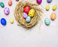 Colored decorative easter eggs with painted faces lie in a nest border ,place for text wooden rustic background top view close Royalty Free Stock Photo