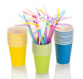 Colored disposable paper cups and straws isolated on white. Royalty Free Stock Photo