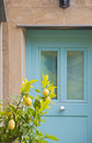 A colored door and a lemon tree in old village in liguria italy Stock Photo