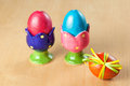 Colored easter eggs in egg cups on wooden table Stock Image