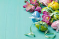 Colored easter eggs and flowers on a turquoise table horizontal shot Stock Photography