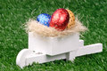 Colored easter eggs and pushcart photo of Stock Images