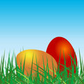 Colored eggs over grass and blue sky Royalty Free Stock Photos