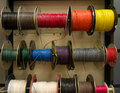 Colored electrical wires on spools on rack Stock Image