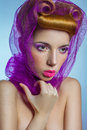 Colored fashion beauty woman with pink tulle and candy colored pearls on her lips and fantasy golden hairstyle on blue background. Royalty Free Stock Photo