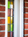 Colored glass window closeup of small windows with white frame in a red brick building Stock Image
