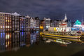 Colored homes on the water in Amsterdam at night Royalty Free Stock Photo