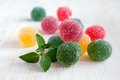 Colored jellies with fresh mint on wooden table Stock Photos